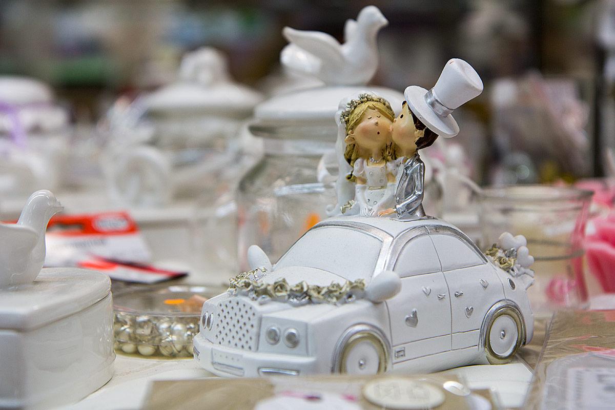 Hochzeitspaar mit geschmücktem Auto
